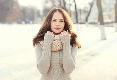 Pretty woman wearing a knitted sweater and scarf outdoors in winter Stock Photography