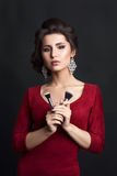 Pretty woman wearing red dress and big earrings holding makeup brushes, posing at camera. Professional make up artist with stylish Royalty Free Stock Image