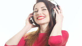 Pretty woman wearing red lipstick listening to the music touching big headphones takes off ear cup saying what isolated on white. Background close up shot stock video footage