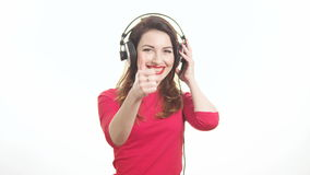 Pretty woman wearing red lipstick listening to the music touching big headphones takes off ear cup saying what isolated on white stock video