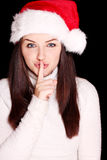 Pretty woman wearing santa hat saying shh stock photo