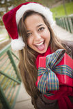 Pretty Woman Wearing a Santa Hat with Wrapped Gift Stock Photography
