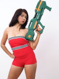 Pretty woman wearing sexy rompers carries toy gun Royalty Free Stock Image