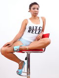 Pretty woman wearing slogan tank top and high heels. Pretty woman wearing high heels sits on red stool Royalty Free Stock Photography
