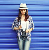 Pretty woman wearing a straw hat and checkered shirt with retro camera Stock Image