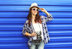 Pretty woman wearing a straw hat, sunglasses, checkered shirt with retro camera Royalty Free Stock Photography