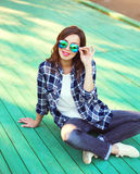 Pretty woman wearing a sunglasses and checkered shirt. Sitting in city Stock Photos