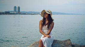 Pretty woman wearing white dress and pamela hat sitting. Over the city beach, sea. Happy summer vacation stock video