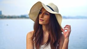 Pretty woman wearing white dress and pamela hat sitting. Over the city beach, sea. Happy summer vacation stock footage
