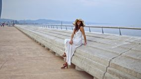 Pretty woman wearing white dress and pamela hat sitting. Over the terrace at sea. Happy summer vacation stock video footage