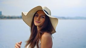 Pretty woman wearing white dress and pamela hat sitting. Over the city beach, sea. Happy summer vacation stock video footage
