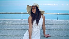 Pretty woman wearing white dress and pamela hat sitting. Over the terrace at sea. Happy summer vacation stock video