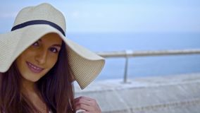 Pretty woman wearing white dress and pamela hat sitting. Over the terrace at sea. Happy summer vacation stock footage