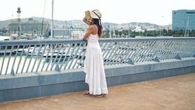 Pretty woman wearing white dress and pamela hat standing. Over the city beach, sea. Happy summer vacation stock video
