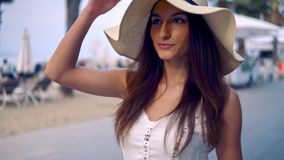 Pretty woman wearing white dress and pamela hat walking. Over the beach terrace at sea. Happy summer vacation stock video footage