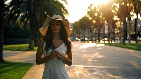 Pretty woman wearing white dress and pamela hat walking. Over the palm green terrace. Happy summer vacation stock video