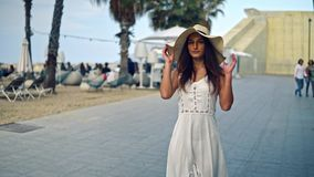 Pretty woman wearing white dress and pamela hat walking. Over the beach terrace at sea. Happy summer vacation stock footage