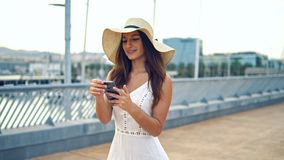 Pretty woman wearing white dress and pamela hat walking. Over the beach terrace at sea. She is talking on a cell phone stock video footage