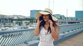 Pretty woman wearing white dress and pamela hat walking. Over the beach terrace at sea. She is talking on a cell phone stock video