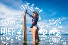 pretty woman in wetsuit with surfboard posing in ocean at Nusa dua Beach Bali Indonesia royalty free stock photo