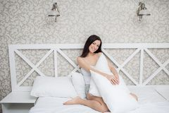 Pretty woman in white bed Royalty Free Stock Image