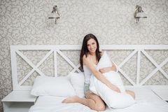 Pretty woman in white bed Stock Image