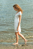 Pretty woman in a white dress on coast Royalty Free Stock Images