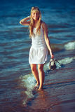 Pretty woman in a white dress on the ocean coast Stock Photos