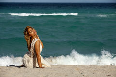 Pretty Woman in white dress sitting on beach Royalty Free Stock Photos