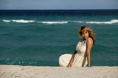 Pretty Woman in white dress sitting on beach Royalty Free Stock Photo