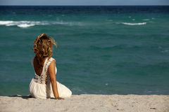Pretty Woman in white dress sitting on beach Stock Photography