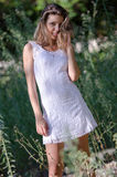 Pretty woman in white dress smiling, beautiful moments in nature behind the greens Royalty Free Stock Photography