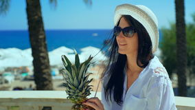 Pretty woman in white hat with tropical cocktail on the beach enjoying sunny weather looking at the ocean view. Positive emotion face expression stock footage