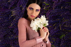 Pretty woman with a white peony in hands Stock Image