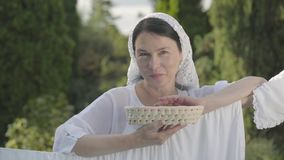 Pretty woman with white shawl on her head eating cherries looking at camera smiling over the clothesline outdoors. Attractive senior woman with a white shawl on stock video footage