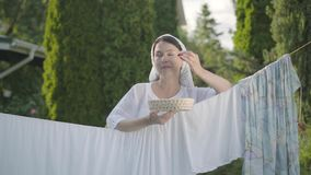 Pretty woman with white shawl on her head eating cherries looking at camera smiling over the clothesline outdoors. Attractive senior woman with a white shawl on stock video