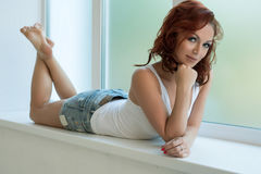 Pretty woman in white top on window sill in studio Royalty Free Stock Image