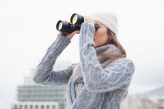 Pretty woman with winter clothes on looking through binoculars Royalty Free Stock Images