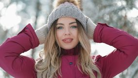 Pretty woman in winter hat smiles standing outside on the snow in the forest. Portrait of a beautiful girl looking into stock footage