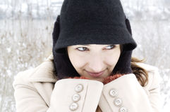 Pretty woman in wintry hat. Attractive young woman in wintry coat and hat covering ears; frozen landscape in background royalty free stock photos