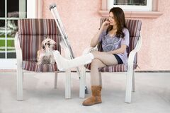Free Pretty Woman With Broken Leg In Cast Relaxing On Chair At Home With Her Dog While Counting Money Stock Image - 185566921
