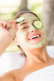 Pretty woman withdrawing a cucumber on her eye Royalty Free Stock Images