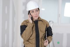 Pretty woman worker on phone at construction site Royalty Free Stock Photography