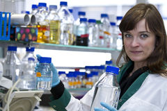 Pretty woman working in biochemistry lab. Wearing blue gloves Royalty Free Stock Images