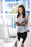 Pretty woman working in bright office smiling Stock Photos