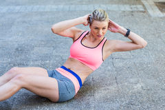 Pretty woman working on her abs Stock Images