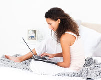 Pretty woman working on her laptop on her bed Royalty Free Stock Image