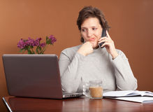 Pretty woman working at home. Pretty brunette working or shopping at a laptop on the kitchen table with a cup of coffee talking on the phone looking worried and Stock Images