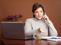 Pretty woman working at home. Pretty brunette working or shopping at a laptop on the kitchen table with a cup of coffee talking on the phone looking worried and Royalty Free Stock Photo