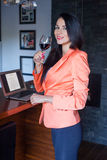 Pretty woman working on laptop at home. Pretty woman working on laptop at home and celebrating her success with red wine Stock Photos